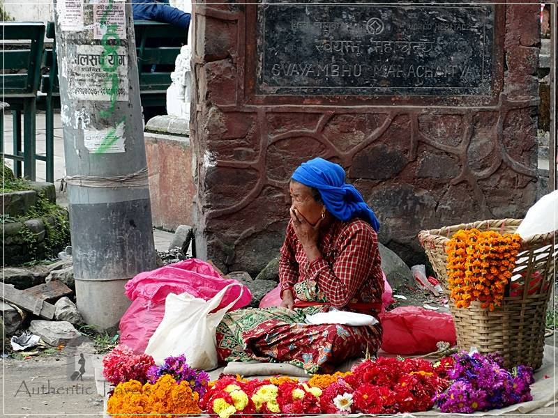 Kathmandu – Swayambhunath Temple: a woman selling flowers for offerings at the temple