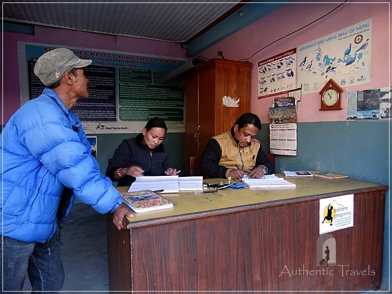 Ghorepani Trek: Birethanti - my guide-porter Salia stamps my permits (tims and national park entrance ticket) at the checkpoint