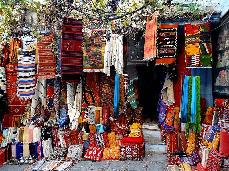 Chefchaouen: colorful shop with colorful carpets